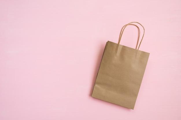 Sacco di carta marrone vuoto con maniglie per lo shopping su uno sfondo rosa