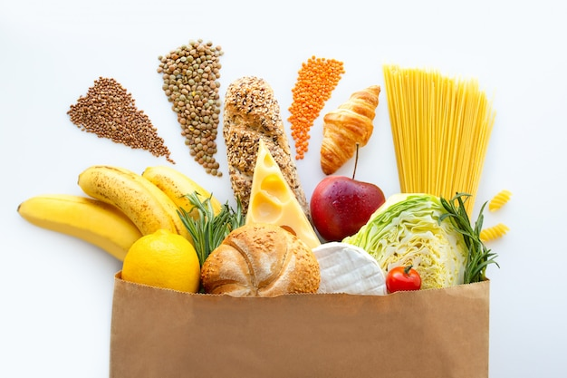 Sacco di carta pieno di cibo sano su uno sfondo bianco. un cesto pieno di frutta e verdura fresca. il concetto di corretta alimentazione. formaggio e cereali consegna del cibo a casa tua. cibi diversi