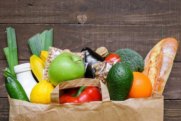 Sacco di carta pieno di cibo vegetariano sano diverso sul tavolo di legno rustico. vista dall'alto