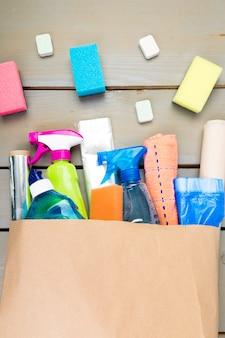 Sacco di carta pieno di diversi prodotti per la pulizia della casa,