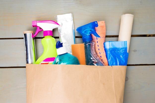 Sacco di carta pieno di diversi prodotti per la pulizia della casa