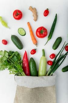 Sacco pieno di verdure sul tavolo bianco