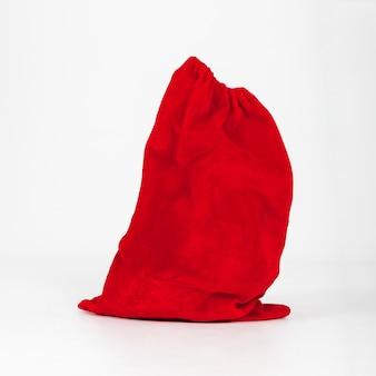 Sacco rosso di regali in piedi su sfondo bianco