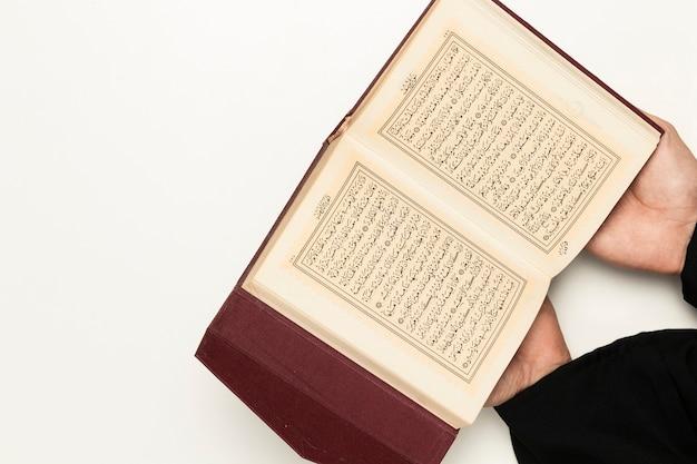 Sacerdote di alto angolo che tiene libro sacro