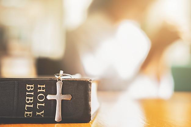 Sacra bibbia e croce sul tavolo con la donna cristiana sperando in qualcosa di meglio.