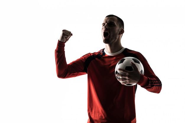 Sagoma di giocatore di calcio calcio uomo in studio isolato su bianco si leva in piedi con una vittoria di palla