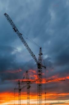 Sagoma di gru edili contro il cielo al tramonto