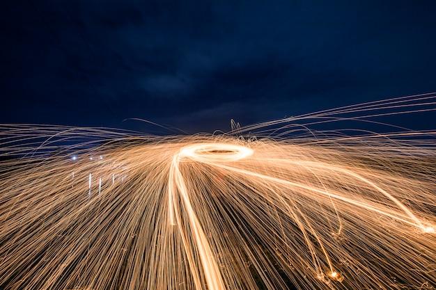 Sagoma di uomo facendo un cerchio di scintille durante la notte