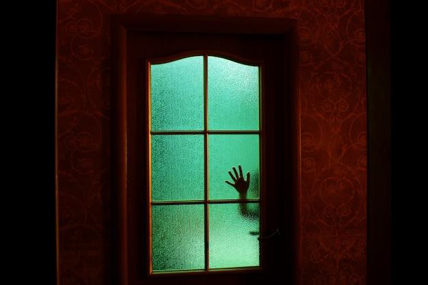 Sagoma scura della mano dietro il vetro in luce verde soprannaturale. bloccato da solo nella stanza dietro la porta di halloween. incubo del bambino con alieni, mostri e fantasmi. il male in casa. all'interno della casa stregata