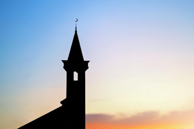 Sagoma scura di una moschea musulmana con mezzaluna sulla guglia al tramonto