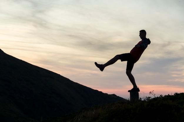 Sagoma scura di una viandante che equilibra su una pietra del vertice nelle montagne di sera.