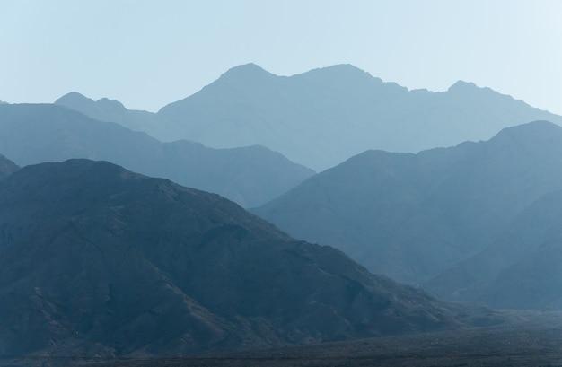 Sagome di catene montuose blu con prospettiva tonale