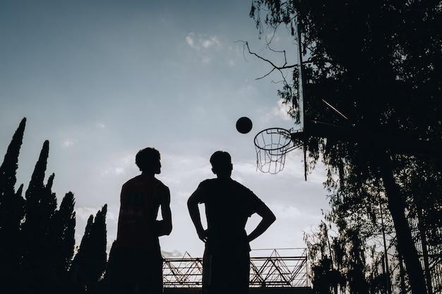 Sagome di due persone che guardano una pallacanestro cadere nel cestino. basket di streetball