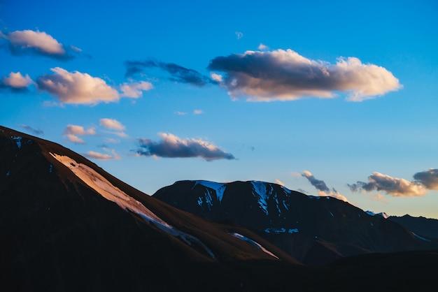 Sagome di montagne innevate con ghiacciai ans cielo al tramonto con nuvole soffici dorate.