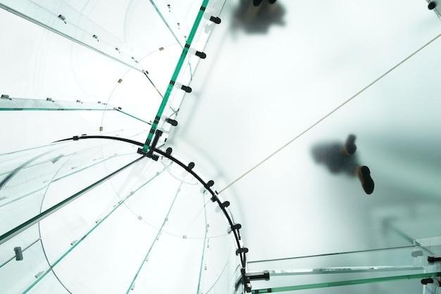 Sagome di persone che camminano su una scala a chiocciola di vetro