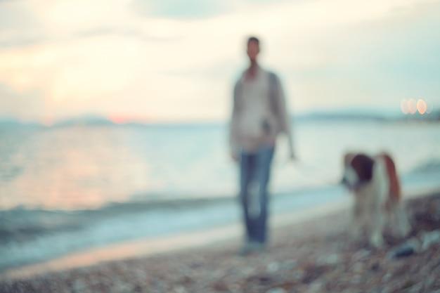Sagome di uomo e cane che camminano lungo la riva del mare. passeggiata serale al tramonto.