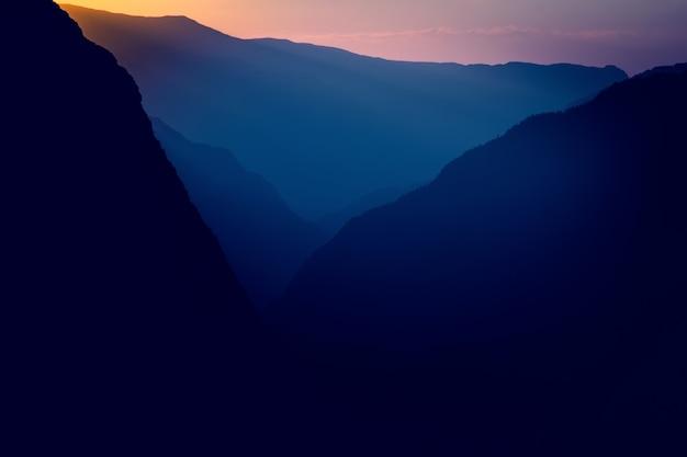 Sagome e contorni di un massiccio montuoso nel sole al tramonto