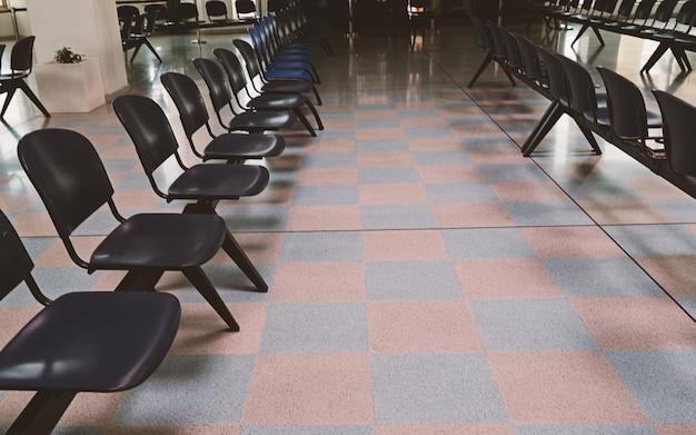 Sala d'attesa alla stazione ferroviaria con sedie vuote