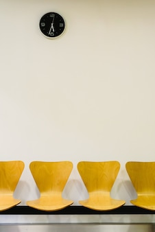 Sala d'attesa con sedie di legno vuote e orologio da parete, in attesa di concetto.