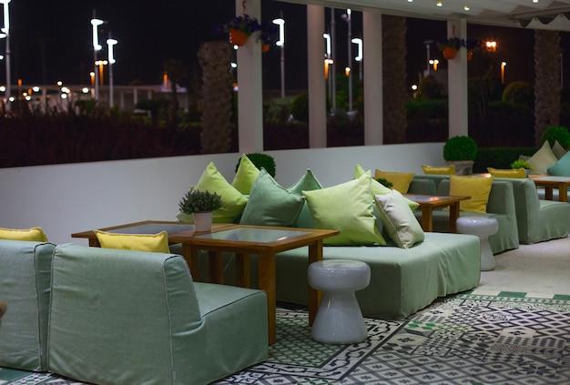 Sala da pranzo, mobili seduti in un bar, ristorante con colori chiari e grandi finestre.