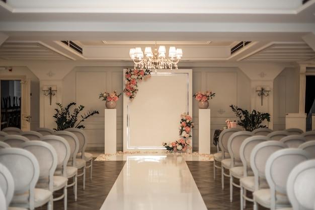 Sala per ricevimenti di matrimonio. file di sedie bianche festive per gli ospiti. arco di cerimonia nuziale per gli sposi.