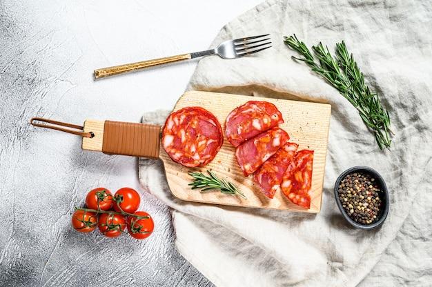 Salame affettato di chorizo. salsiccia chorizo tradizionale spagnola. sfondo grigio. vista dall'alto
