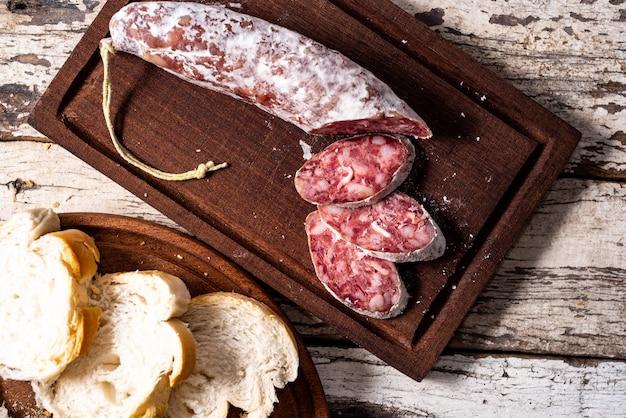 Salame e pane su una tavola di legno