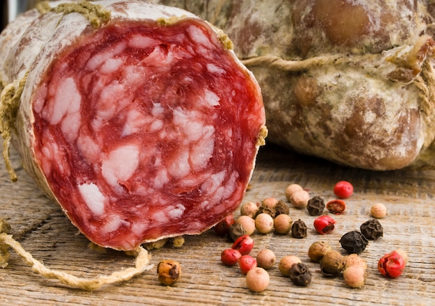 Salame italiano vicino alle spezie sulla tavola di legno