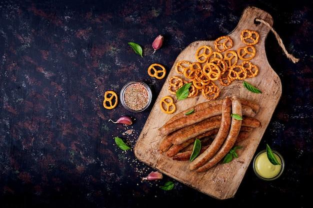 Salatini e salsicce alla griglia su sfondo scuro. oktoberfest. disteso. vista dall'alto