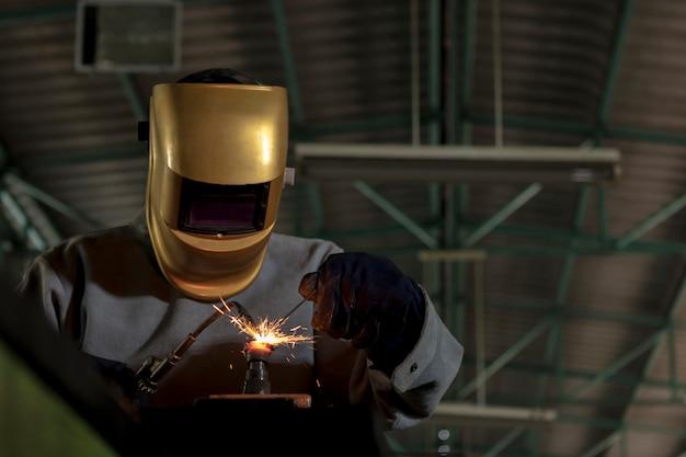 Saldatore del lavoratore che lavora l'acciaio del gas della saldatura nell'industria con i guanti della maschera di sicurezza e le attrezzature di sicurezza.