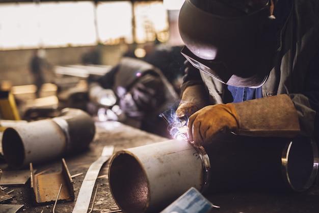 Saldatore in uniforme protettiva e maschera saldatura tubo metallico sul tavolo industriale mentre volano scintille.