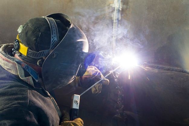 Saldatura del guscio dello scambiatore di calore. un saldatore salda tubazioni tecnologiche con saldatura ad arco manuale per una raffineria di petrolio in russia. giunto saldato