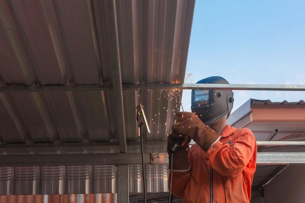 Saldatura del lavoratore nella saldatura di indumenti da lavoro arancioni per capriata del tetto