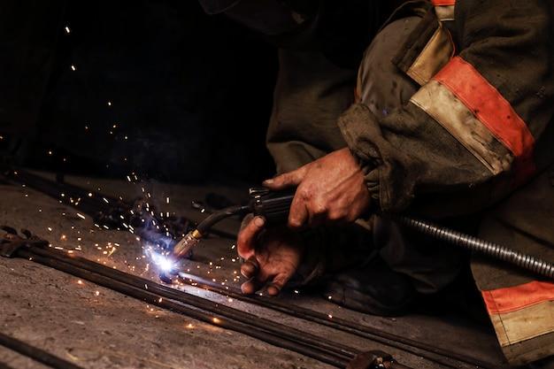 Saldatura uomo in garage saldatura manuale, scintille, ferro
