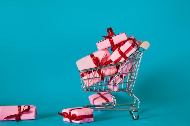 Saldi delle vacanze, concetto. un sacco di scatole regalo rosa nel carrello.