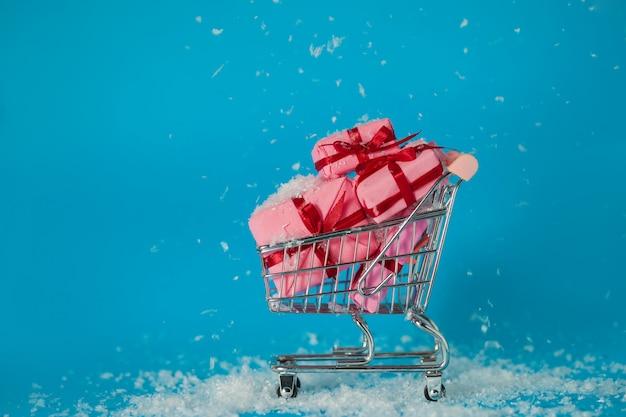 Saldi di natale. l'acquisto di regali per il nuovo anno, il concetto. il carrello è pieno di scatole regalo