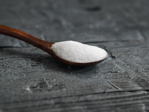 Sale bianco, macinato finemente sparso su un tavolo di legno scuro con un cucchiaio