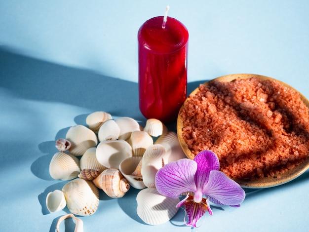 Sale da bagno arancione in un piattino con conchiglie, candela rossa e fiore su uno sfondo blu con un'ombra da una pianta tropicale. copyspace. spa, rilassata, estate