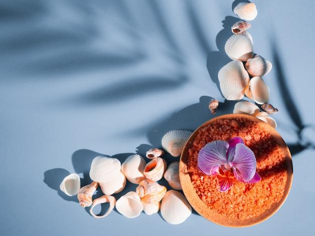 Sale da bagno arancione in un piattino con conchiglie e fiori su sfondo blu con un'ombra da una pianta tropicale. copyspace, flatlay. spa, rilassata, estate