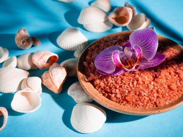 Sale da bagno arancione in un piattino con conchiglie e fiori su sfondo blu con un'ombra da una pianta tropicale. copyspace. spa, rilassata, estate