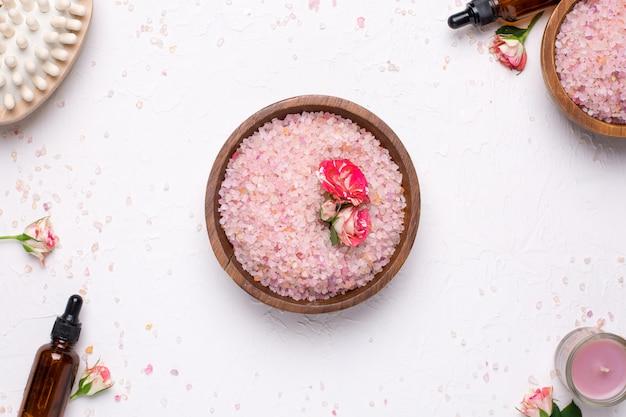 Sale da bagno rosa con fiori e bottiglie di olio naturale su bianco