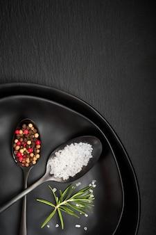 Sale in pepe misto in cucchiai vintage sul vecchio piatto di metallo con tovagliolo di lino su pietra grigio scuro