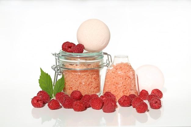 Sale marino con estratto di lampone. cosmetici alla fragola. sale da bagno rosa in vasetti di vetro e lamponi.