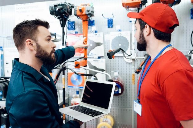 Salesmen sta lavorando nel negozio di utensili elettrici