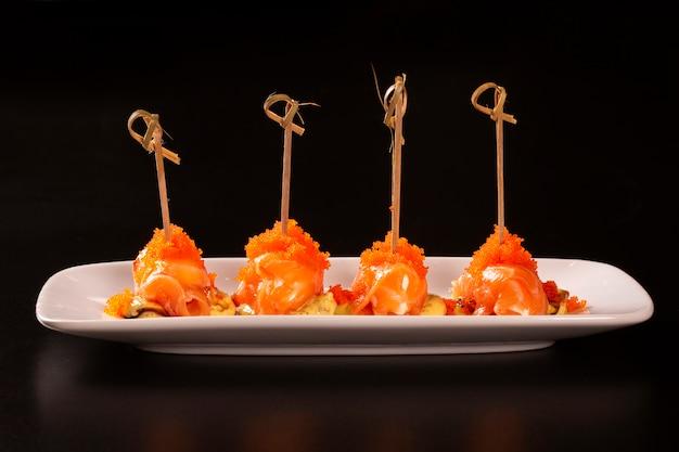 Salmon eggs o ikura sushi e salmon roe sushi in sushi in stile giapponese fresco dal pesce crudo di salmond sul piatto bianco.