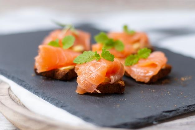 Salmone affumicato su pane tostato con burro con foglia di menta su pietra nera e vecchia tavola di legno