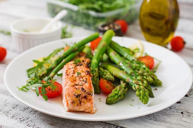 Salmone al forno guarnito con asparagi e pomodori con erbe