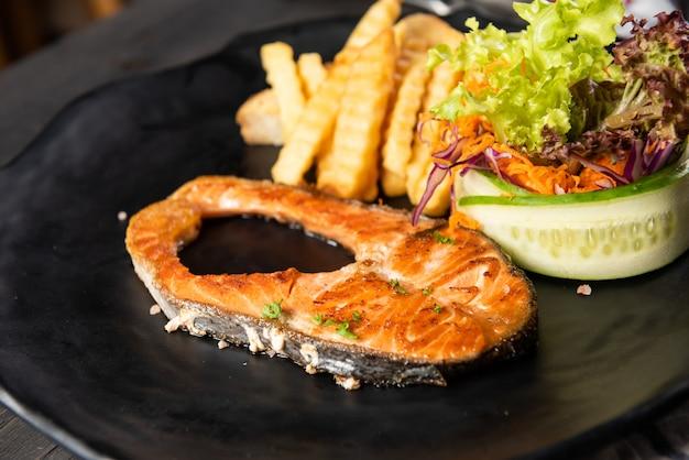 Salmone alla griglia con patatine fritte e insalata