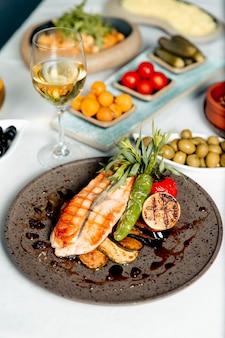 Salmone alla griglia con verdure e limone servito con un bicchiere di vino