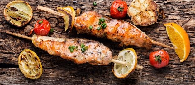 Salmone alla griglia con verdure sulla tavola di legno. pesce grigliato con limone
